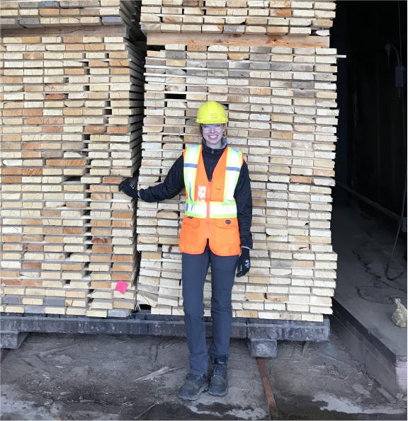 Alexa Gilbert standing in front of a lumber charge in a dry kiln